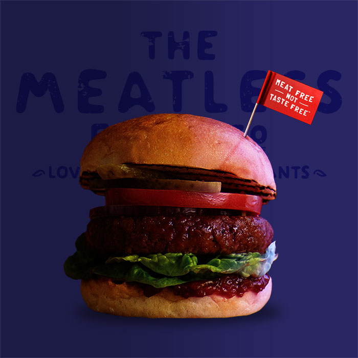 Thick Meatless Burger on a bun with tomato, lettuce and pickles